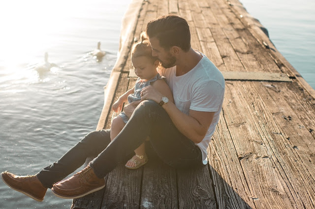 Man with young daughter sitting on a wooden jetty watching the swans swim by