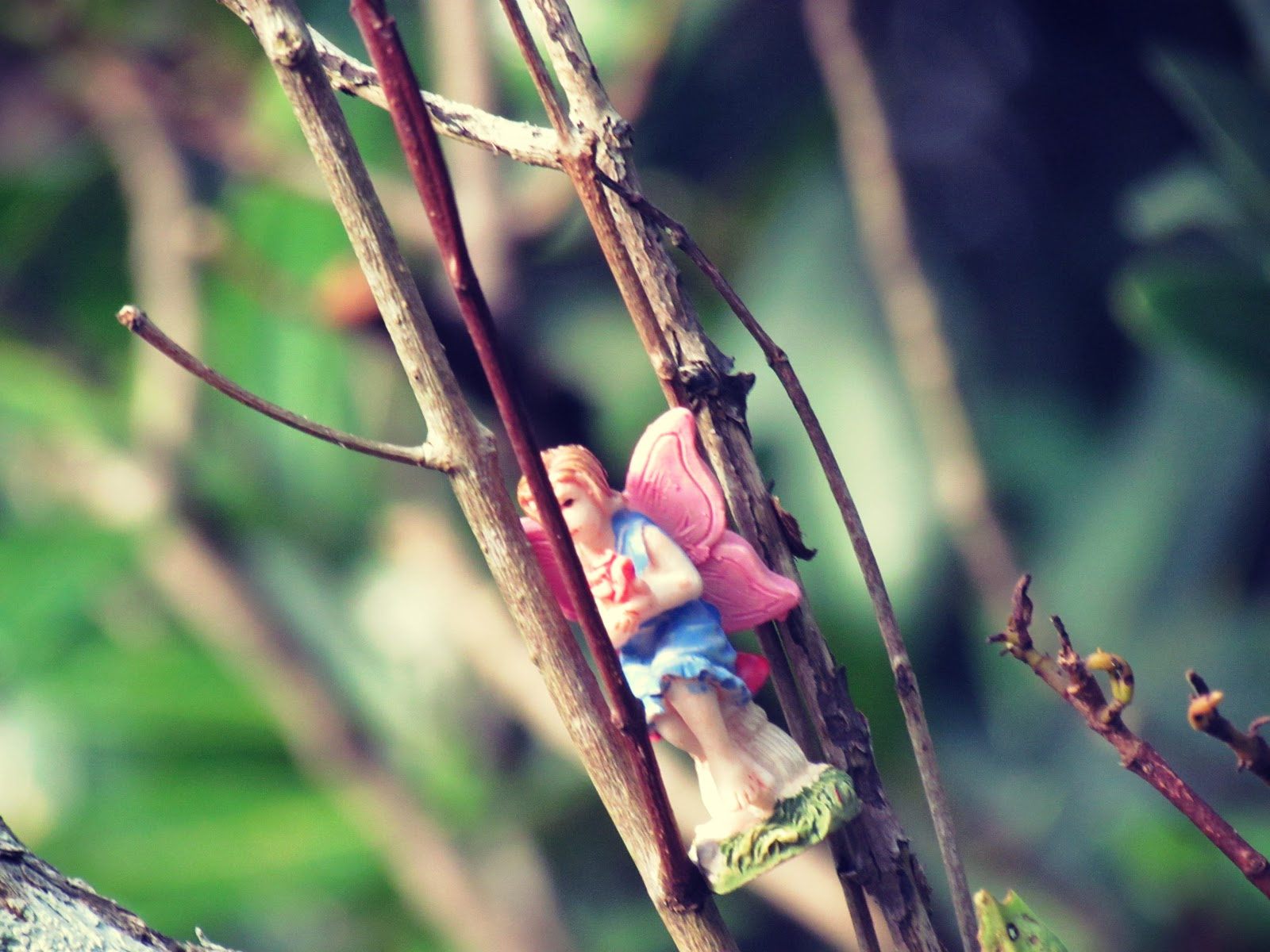 A fairy hidden in plain sight with fairy figurine nestled in tree branches and twigs