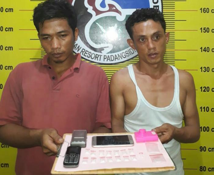 Kedua tersangka saat di kantor polisi.