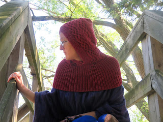 A woman wearing a red knit hood, with a cabled-stitch border around the front of the hood.  The hood has a ribbed neck that falls over the top of the shoulders.