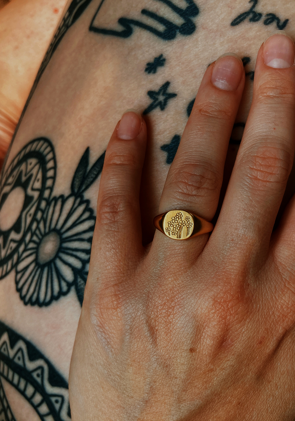 Close up of hand wearing Daisy forget me not signet ring, with tattooed legs in the background