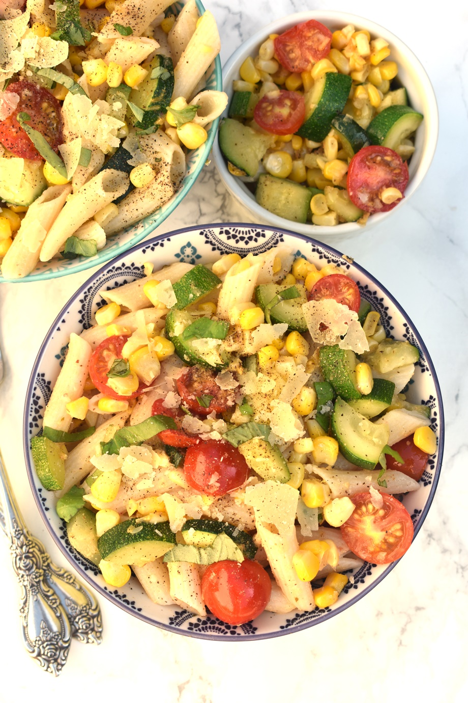 Tomato, Zucchini and Corn Pasta Salad is loaded with fresh sauteed vegetables, shaved parmesan cheese and Caesar vinaigrette for a delicious lunch that is perfect for meal prep!