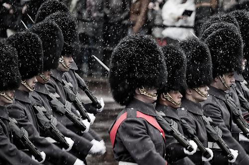 Os guardas da rainha da Inglaterra em marcha sob a neve (tem um que parece dormir).