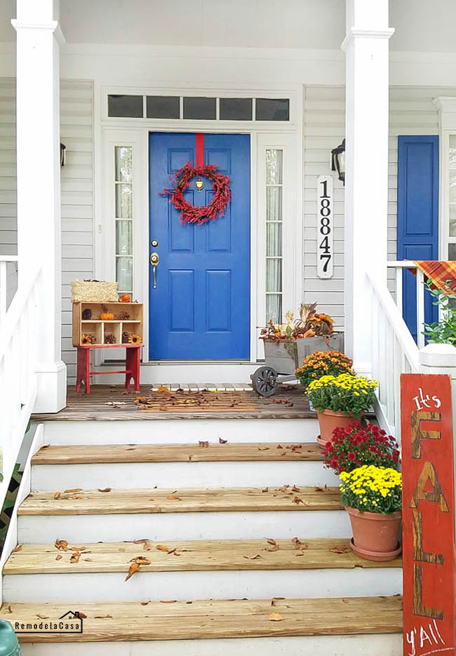 front porch with blue door and shutters, mums, red berry wreath, pinecoens