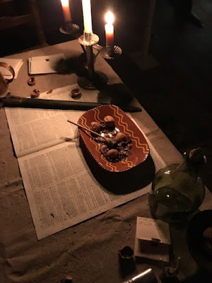 Candles light a table with a redware dish full of walnuts. An repro newspaper and glass bottle are also on the table.