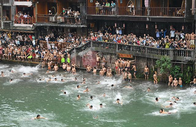 multitud de personas a orillas del río esperan para lanzarse al agua
