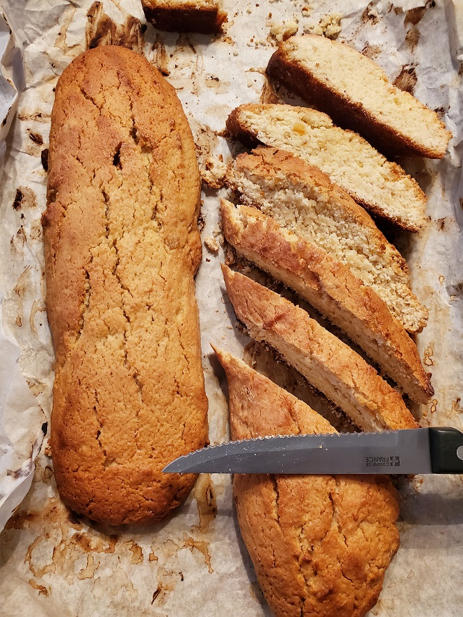 these are Italian biscotti cooling and then sliced with a serrated edged knife to be toasted on a cookie sheet with parchment paper