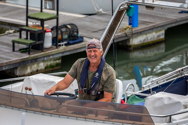 Photo of Phil at the helm on Ravensdale's flybridge. Photo by Ronnie Bell
