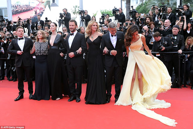 Amal Clooney found herself struggling with the flowing train of her gorgeous gown as she attended the premiere of her husband's new film Money Monster at the 69th annual Cannes Film Festival