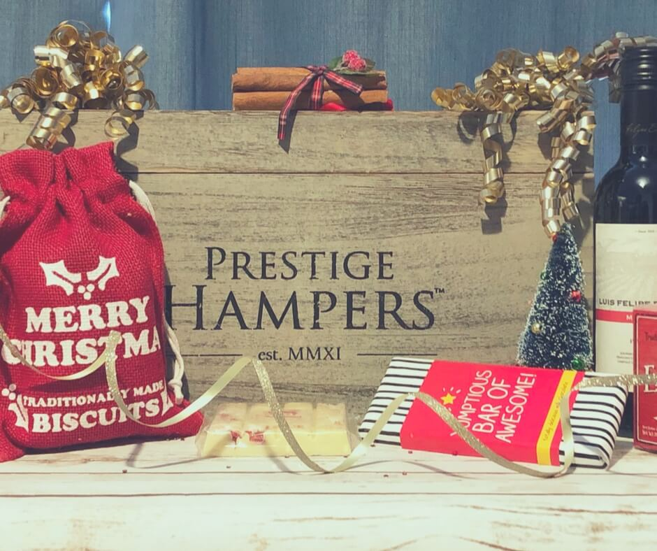 "Vintage wooden box from Prestige Hampers decorated with golden Christmas decorations. A  small red sack reading ""merry Christmas"" sits in front of the box, alongside a bar of white chocolate."