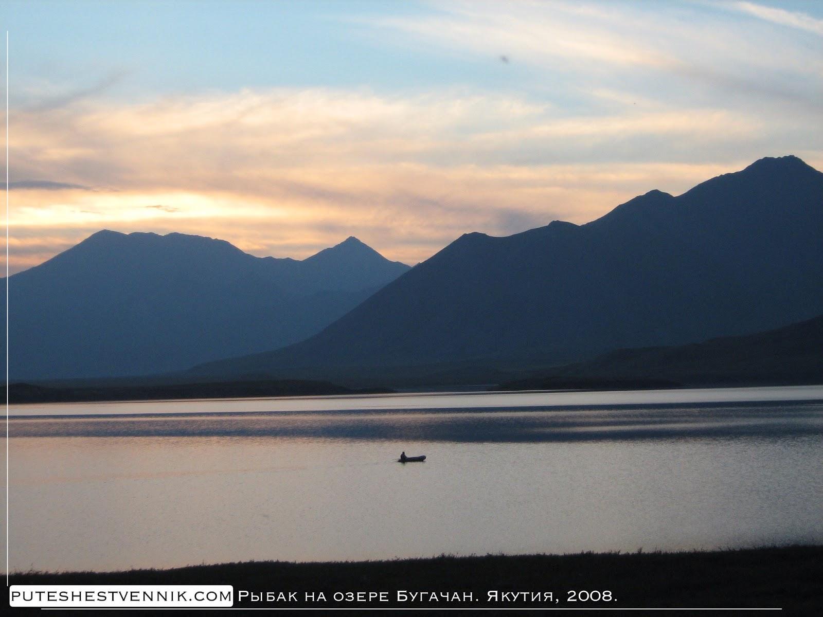 Рыбак в лодке на озере Бугачан и горы