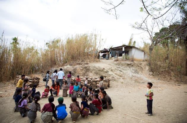 A imagem mostra um círculo de crianças em volta de um missionário numa tribo do interior africano.