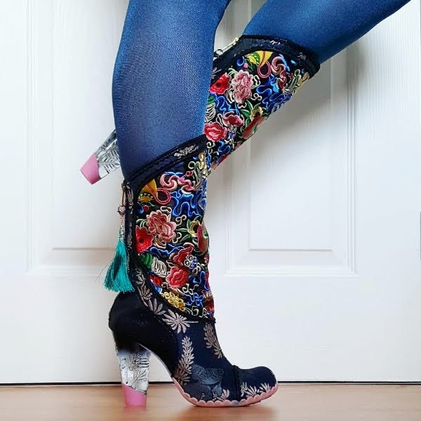 side view wearing knee high colourful embroidered boots with shaded perspex heel and tassel zip at back