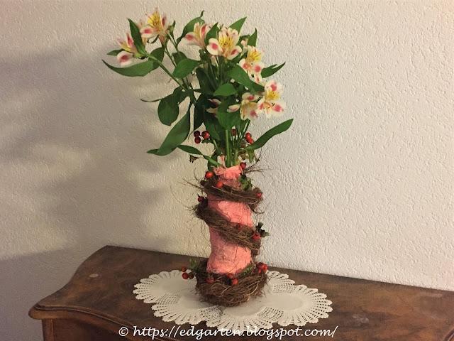 Vase mit Alstromerien und Hagebutten