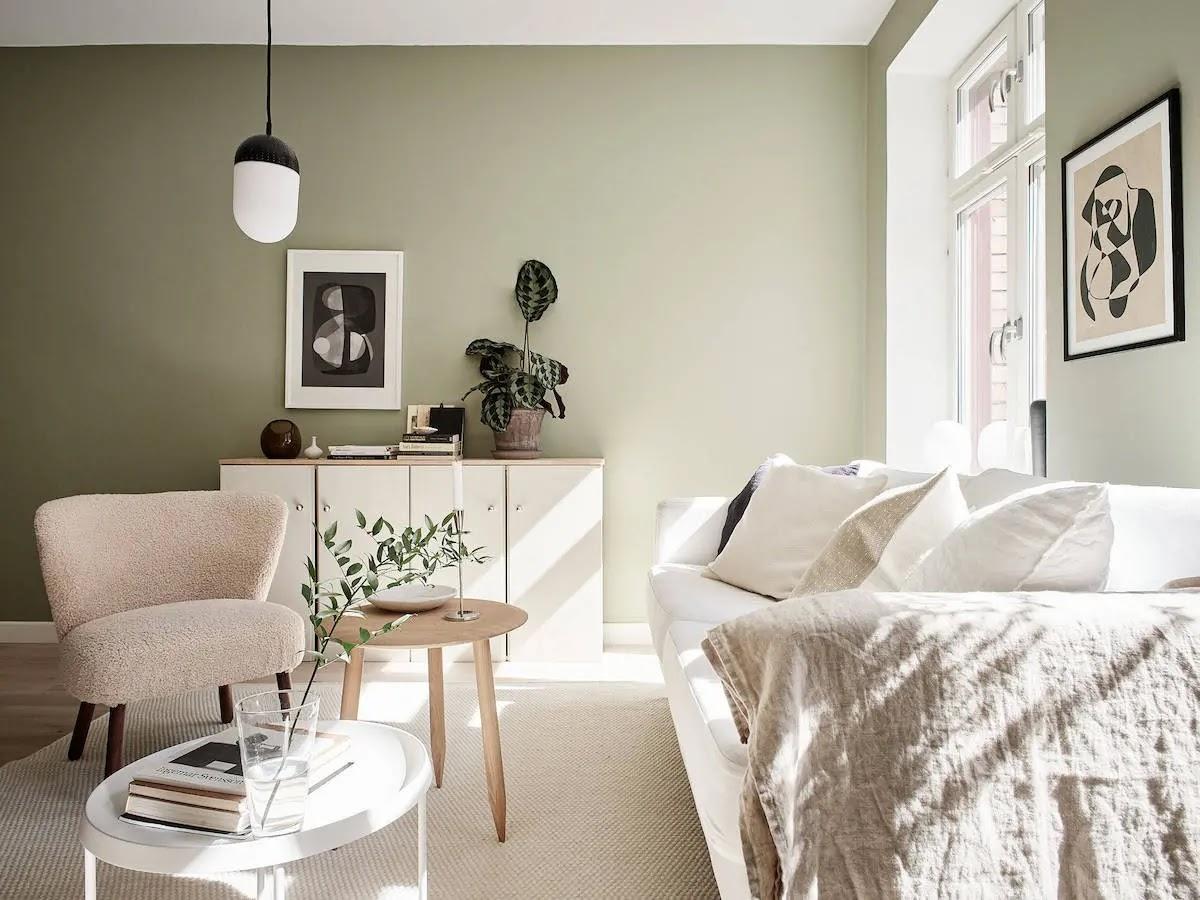 Salón de estilo nórdico con muebles blancos y paredes pintadas de verde