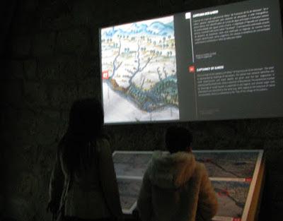 mãe e filho observando painel no Centro Interpretativo dos Descobrimentos na Casa do Infante