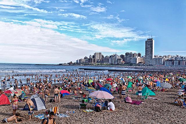 Playa colmada de gente, el mar y la ciudad.