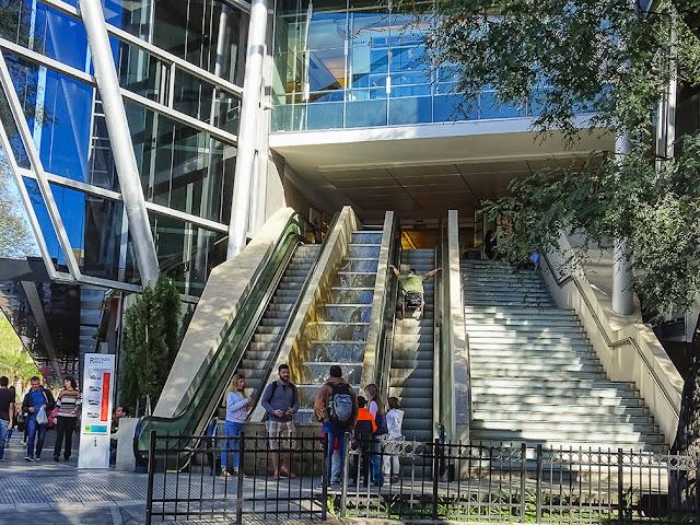 Frente al Recoleta Mall gente charlando y una persona subiendo las escaleras.