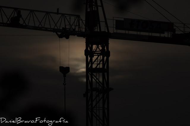 Fotografía en primer plano de una grúa de obra con el Sol detrás entre nubes haciendo un bonito contraluz