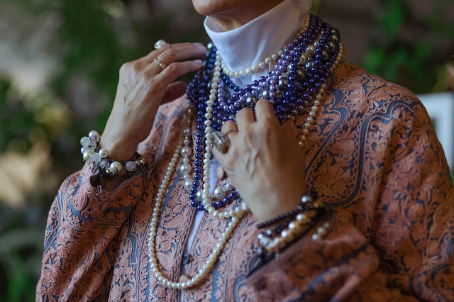 A person wearing different beaded necklaces.