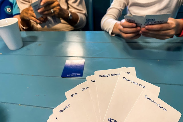 A hand of 10 answer cards from Kids Against Maturity being held while playing the game with family on holiday to review the card game