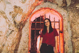 Laura is standing inside of a cave. She is wearing a red shirt
