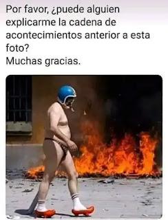Hombre en calzoncillos y con casco pasándose por delante de un incendio