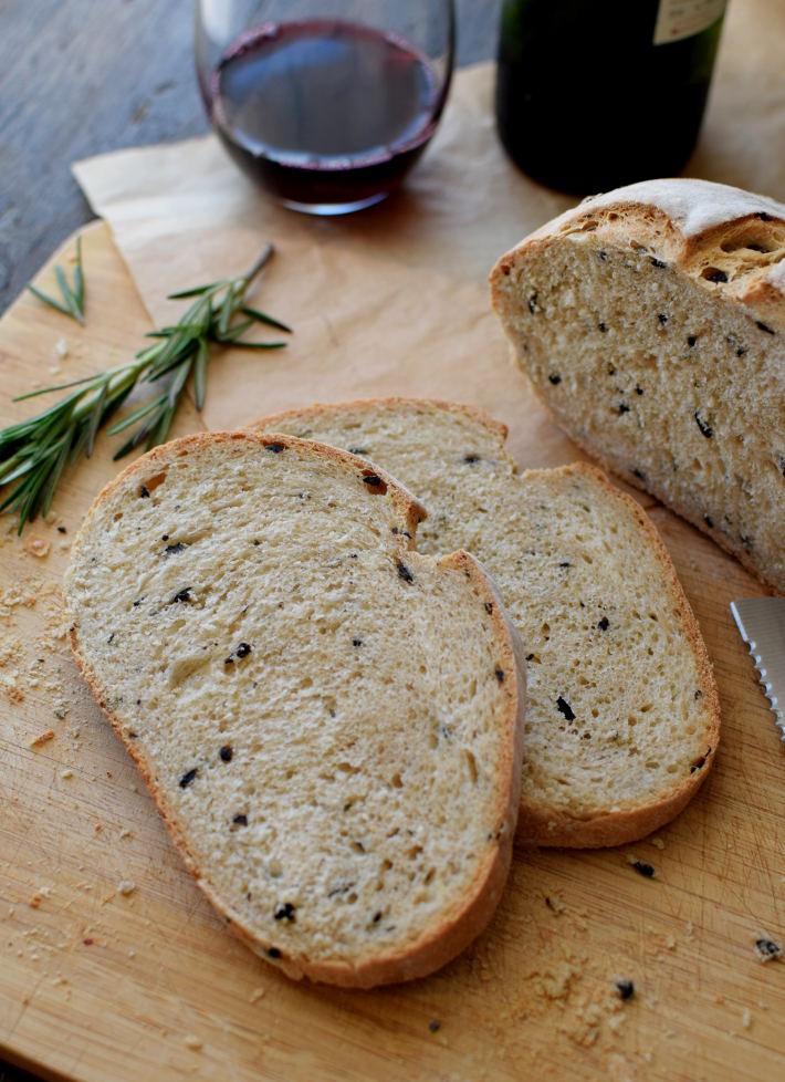 Pan rústico con aceitunas y romero, servido con vino y queso
