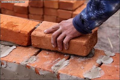 assentando tijolos maciços