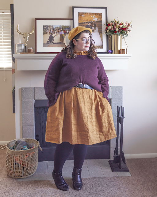 An outfit consisting of a yellow beret, a purple sweater belted over a yellow collared linen dress and black boots.
