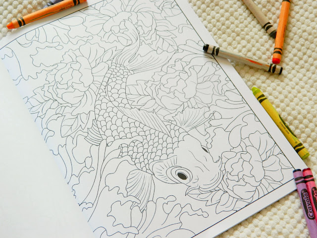 A colouring page showing a huge koi carp fish surrounded by flowers in a Japanese art style