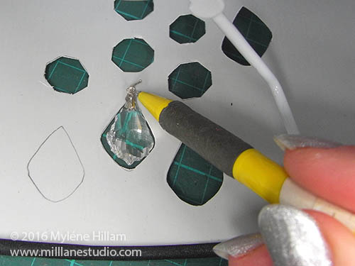 Place the crystal in a corresponding cut out and mark the position of the top prong.