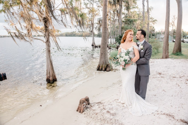 bride and groom smile at beach