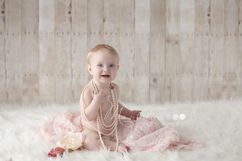 Cute baby girl playing with pearls and flowers