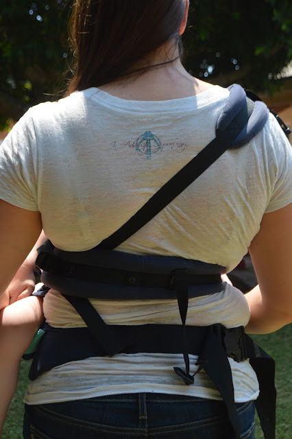Back image of the wearer showing one shoulder strap at a diagonal across her back, the other shoulder strap across her waist, and the waistband straps at her hips.