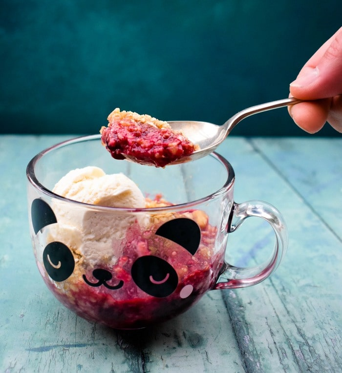 A spoonful of blackberry crumble lifted out of a glass mug