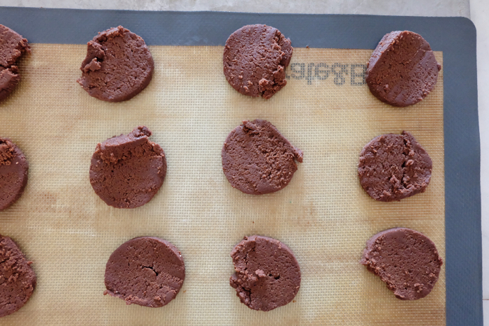 cookie dough round slices on silicone baking mat