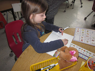 Student playing school with a stuffie.