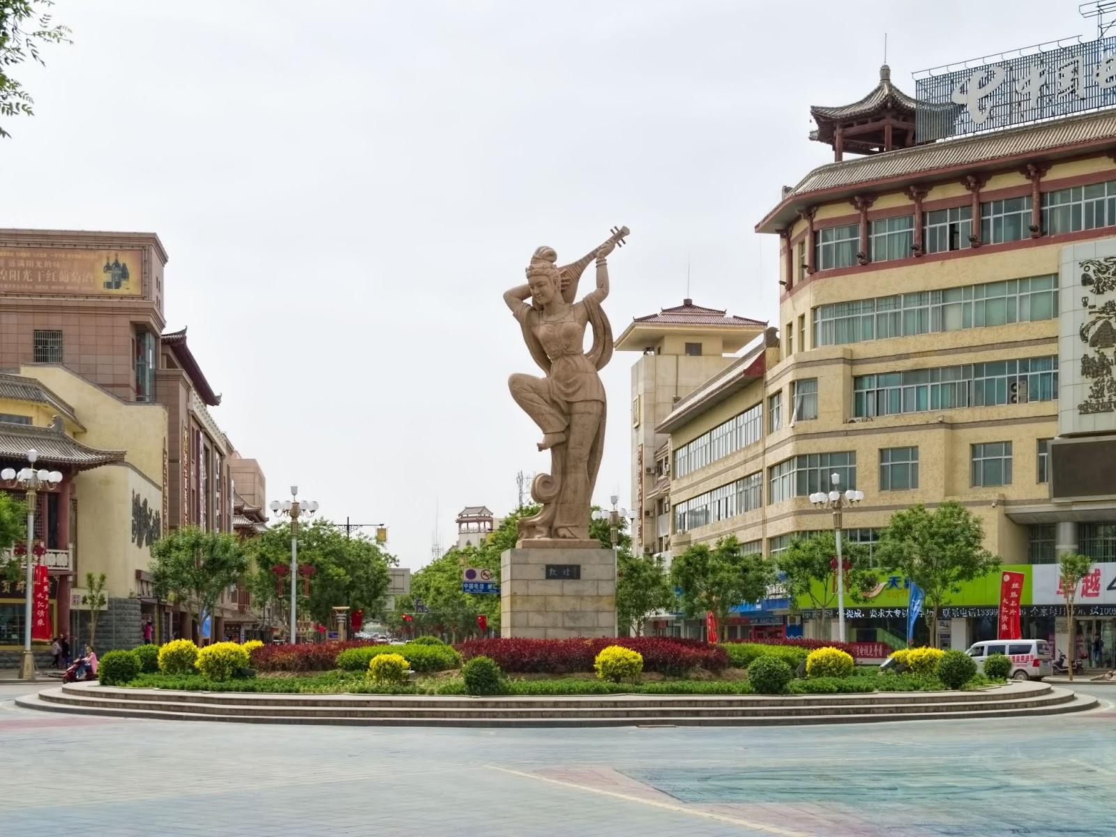 O símbolo da cidade de Dunhuang: a estátua de Fan Tan Pipa representando uma mulher dançando e tocando, nas costas, um pipa (alaúde de quatro cordas chinês).