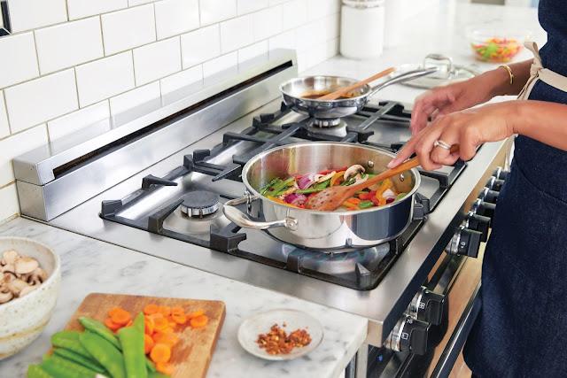 Mulher no fogão cozinhando legumes na cozinha