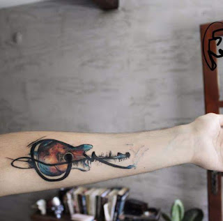 Tatuaje de guitarra a color en el antebrazo