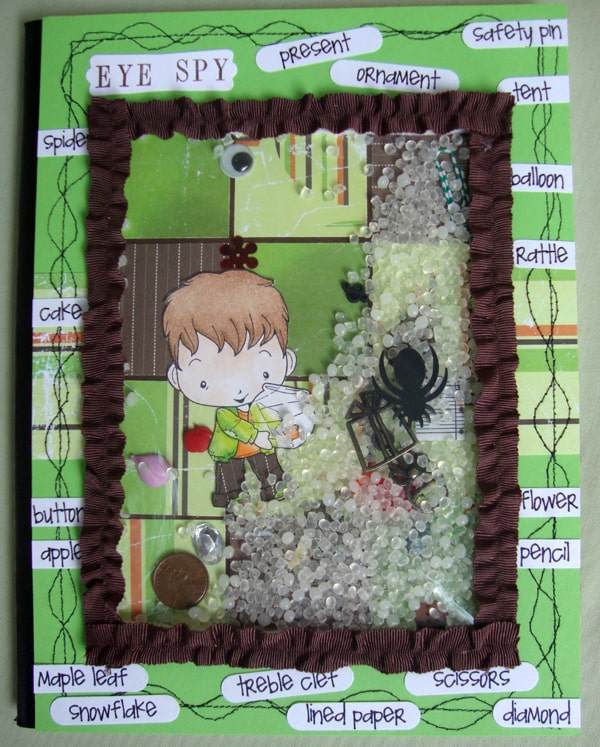 "This cute altered notebook is a piece of acetate covered in ribbon...mounted with foam and filled with little ""I Spy"" items to find. This book would be great for kids that need a little stimulation periodically."