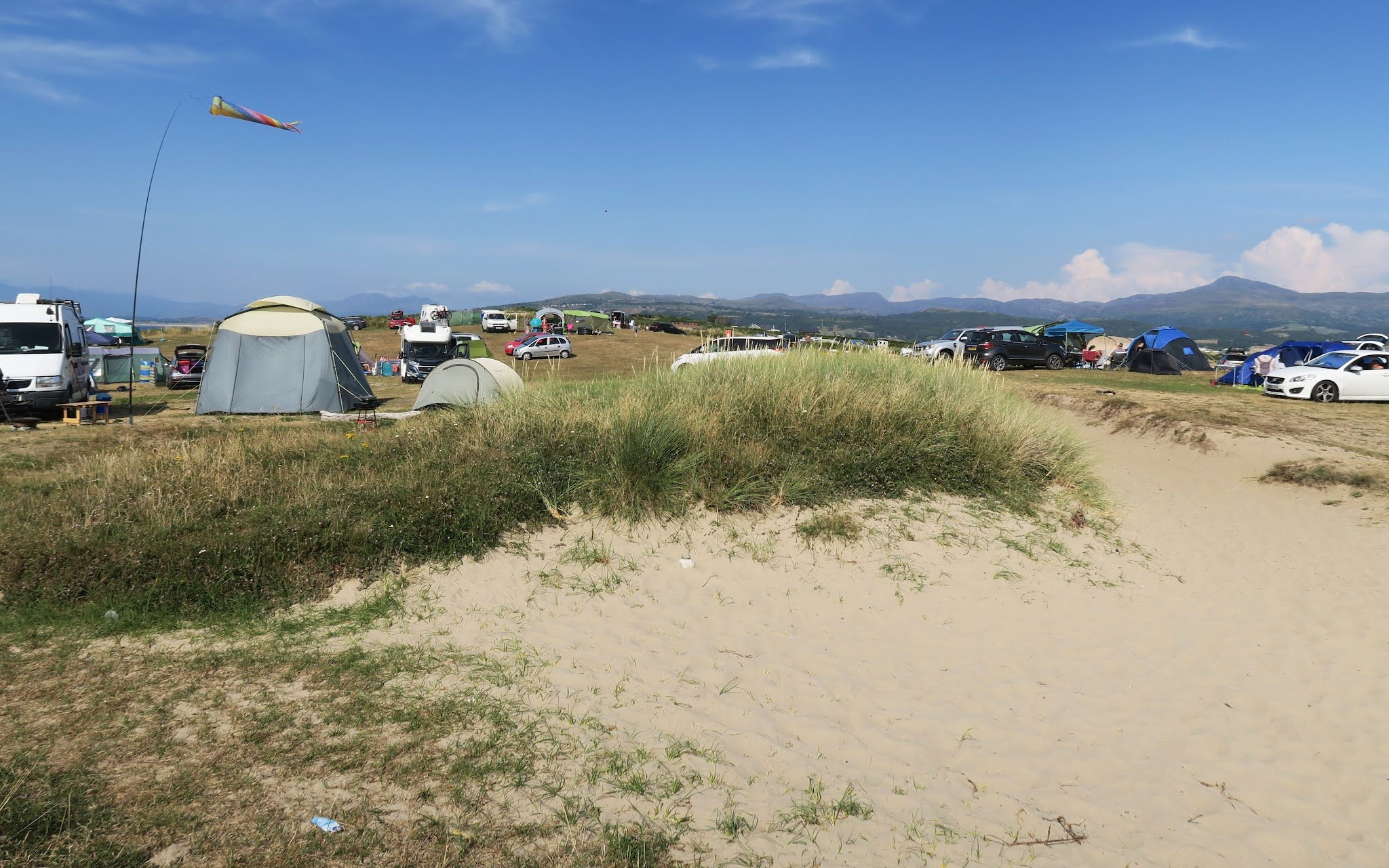 Standing on a sandy path looking towards the campsite. Tents and campervans can be seen across the landscape.