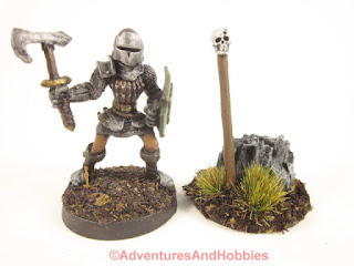 28mm scale miniature stands next to style T1581 skull totem.