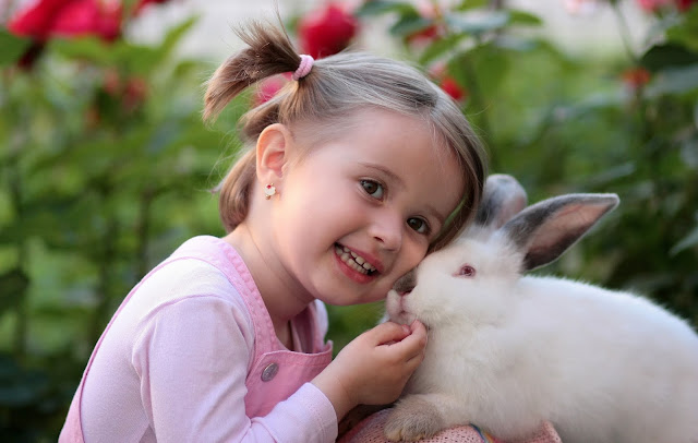 Little girl in pink with her pet bunny.