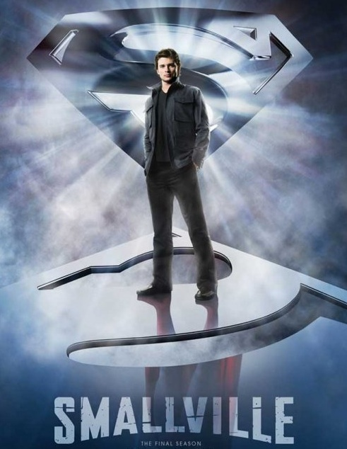 Tom Welling as Clark Kent dressed in black standing atop an mirror-like Superman emblem which reflects him up to his waist in the familiar blue suit, red boots, and cape