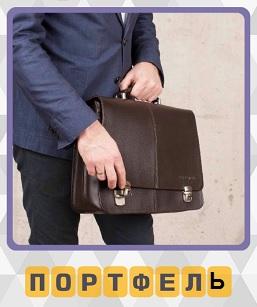 мужчина держит в руках портфель и пытается его открыть