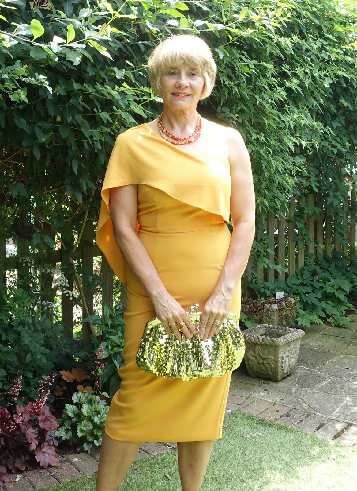 A statement dress for the mother of the bride or groom who doesn't want to look old fashioned. Egg yolk yellow dress by Lavish Alice with flattering draping over one arm