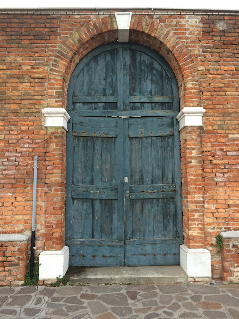Murano glass factory blue door with brick
