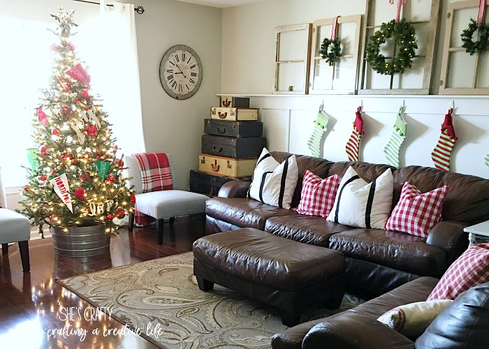 brown leather couches, Christmas pennants, windows, red checked pillows